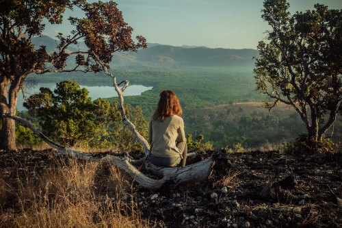 A young woman is sitting on a hill damaged by wild fires at sunrise
