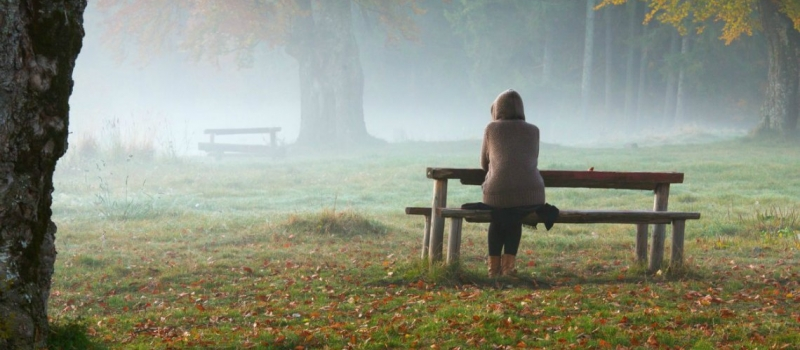 Woman relaxing on a bench in a foggy morning